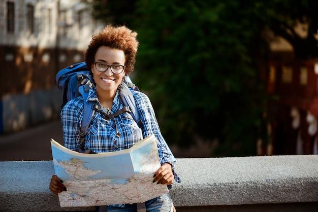 Joven viajero africano hermosa mujer con mochila sonriendo, sosteniendo el mapa.