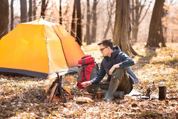 Un joven viajero en el bosque está descansando cerca de la tienda y desayunando en la naturaleza.