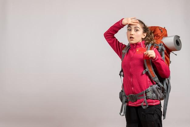 Joven viajero cansado con mochila grande sosteniendo billete de viaje en gris