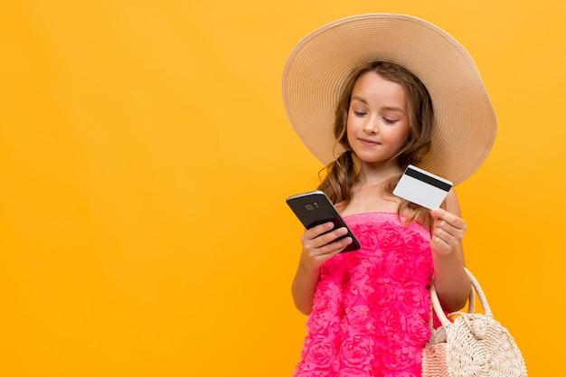 Joven viajero caucásico en un sombrero de paja con una bolsa redonda tiene una tarjeta de crédito con una maqueta y un teléfono en una pared amarilla