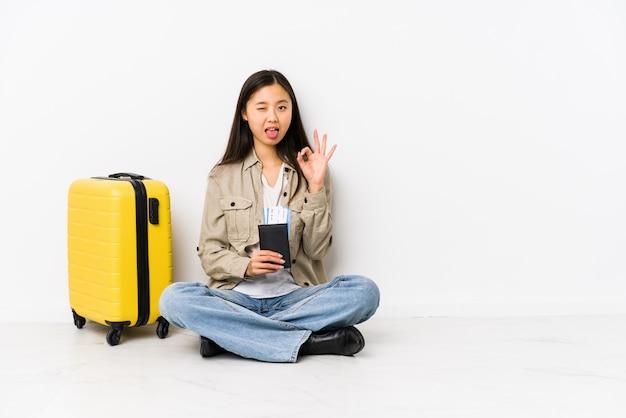 Joven viajero chino mujer sentada sosteniendo una tarjeta de embarque guiña un ojo y tiene un gesto bien con la mano.