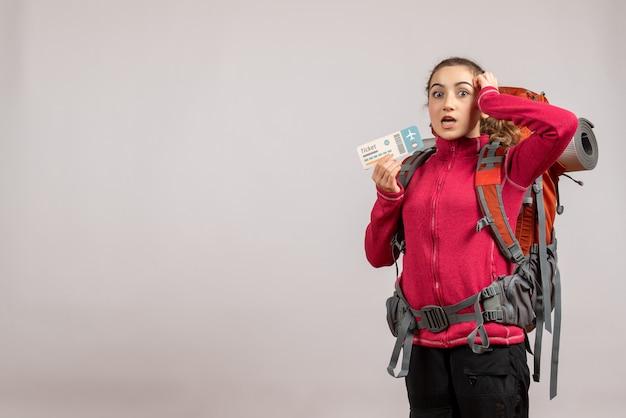 Joven viajero desconcertado con mochila grande sosteniendo un boleto de viaje en gris