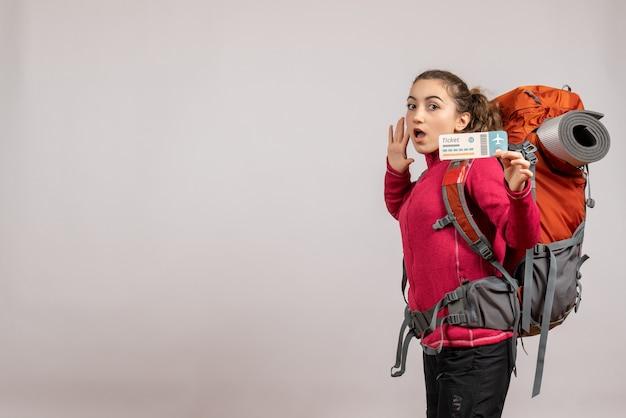 Joven viajero desconcertado con mochila grande sosteniendo un boleto de viaje