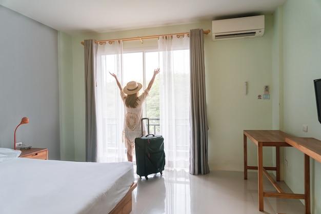Joven viajero con equipaje mirando la vista en la habitación del hotel en vacaciones de verano