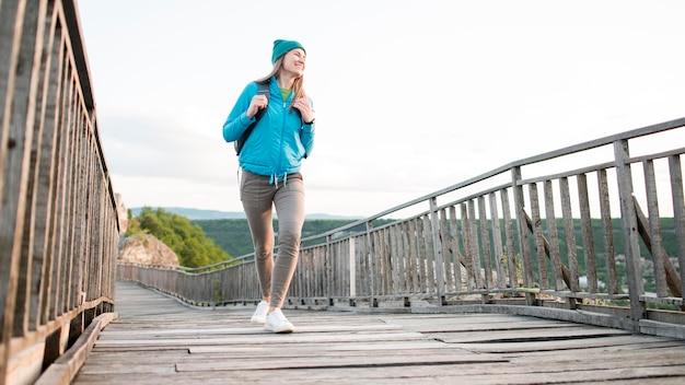 Joven viajero con gorro caminando sobre el puente