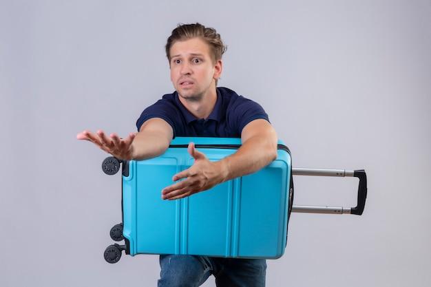 Joven viajero guapo chico de pie con la maleta mirando a un lado con expresión confusa gesticulando con las manos sobre fondo blanco.