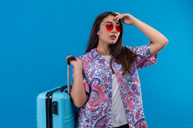 Joven viajero hermosa mujer con gafas de sol rojas con maleta azul mirando a un lado con expresión pensativa teniendo dudas sobre la pared azul