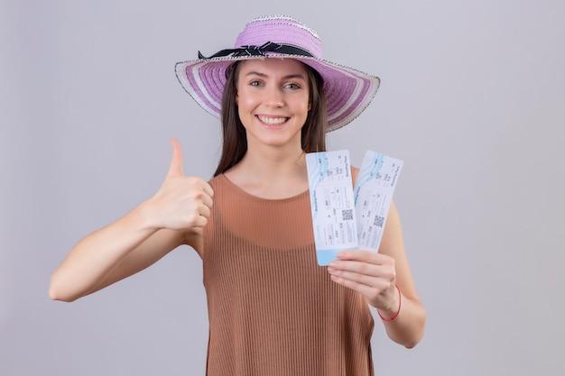 Joven viajero hermosa mujer con sombrero de verano con boletos aéreos sonriendo con cara feliz mostrando los pulgares para arriba sobre la pared blanca