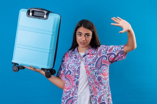 Joven viajero hermosa mujer sosteniendo la maleta azul levantando la mano en señal de rendición de miedo sobre la pared azul