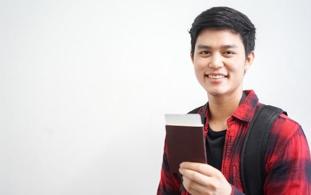Joven viajero hombre sonríe y tiene pasaporte con boleto