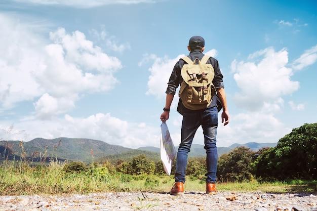 Joven viajero con mochila relajante al aire libre.