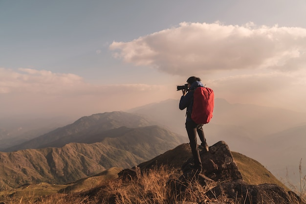 Joven viajero con mochila tomando una foto en la montaña