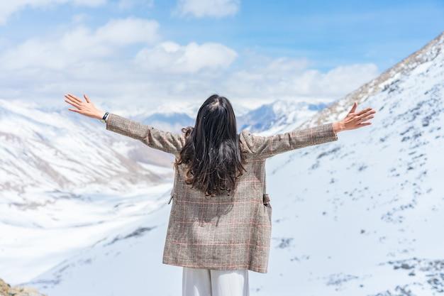 Joven viajero mujer asiática disfrutando en la cima de la montaña de nieve en leh, ladakh, india