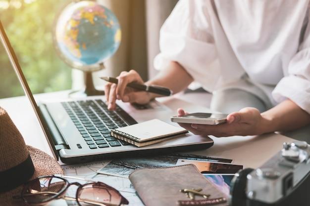 Joven viajero que planea un viaje de vacaciones y busca información o reserva un hotel en una computadora portátil