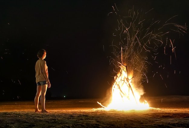 Joven viajero siente el calor de la hoguera de playa con chispas en la noche
