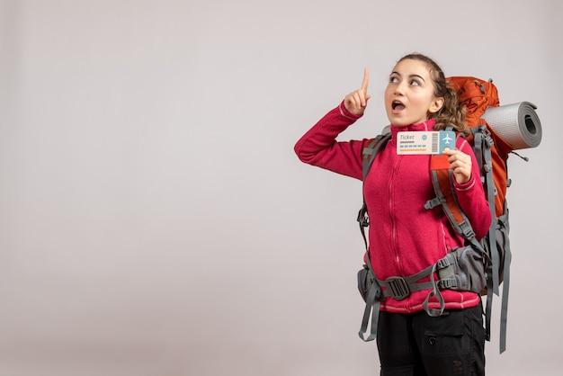 Joven viajero sorprendido con mochila grande sosteniendo el billete de viaje apuntando con el dedo hacia arriba