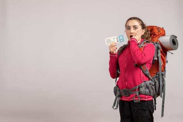 Joven viajero sorprendido con mochila grande sosteniendo el boleto de viaje