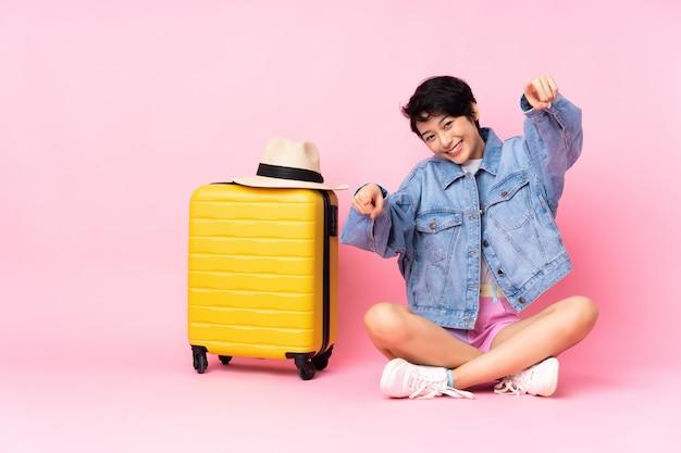 Joven viajero vietnamita con maleta sentada en el suelo sobre la pared rosa señala con el dedo mientras sonríe