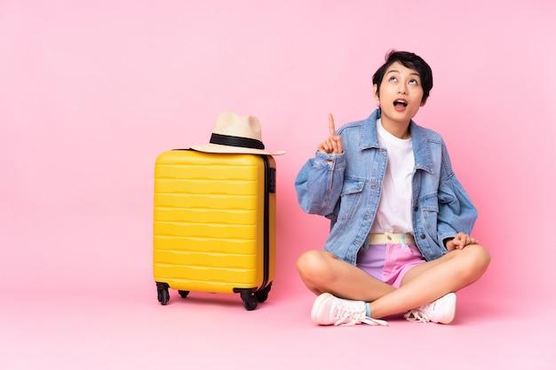 Joven viajero vietnamita con maleta sentada en el suelo sobre rosa aislado apuntando hacia arriba y sorprendido