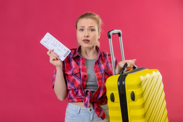 Joven viajero vistiendo camisa roja con maleta y boleto en pared rosa aislada