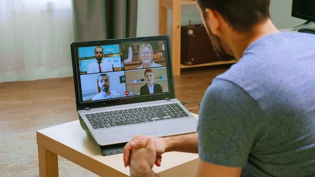 Joven en una videoconferencia con sus colegas durante el aislamiento del covid-19.