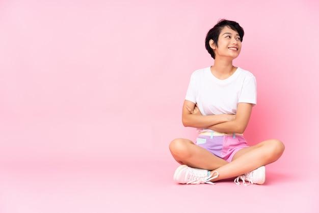 Joven vietnamita con el pelo corto sentada en el suelo sobre la pared rosa aislado con los brazos cruzados y feliz