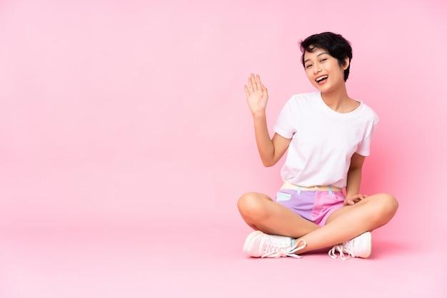 Joven vietnamita con el pelo corto sentada en el suelo sobre la pared rosa saludando con la mano con expresión feliz