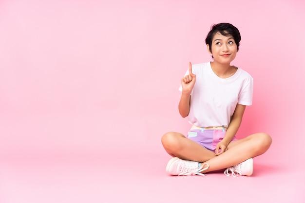 Joven vietnamita con el pelo corto sentada en el suelo sobre rosa aislado