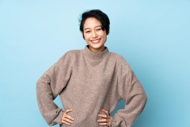Joven vietnamita con pelo corto sobre pared aislada posando con los brazos en la cadera y sonriendo