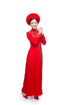 Joven vietnamita vestida de ao dai con gesto de oración deseándole buena suerte