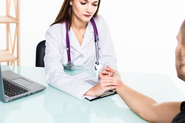 El joven vino a ver al doctor. el médico mide el pulso del paciente en el consultorio.