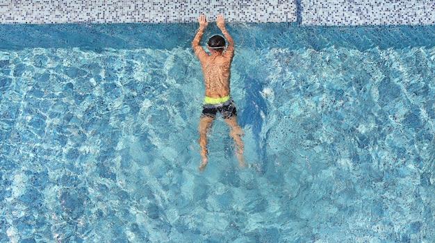 Joven vista superior relajante en la piscina con espacio de copia