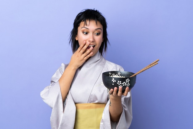 Joven vistiendo kimono sobre azul aislado con sorpresa y expresión facial sorprendida mientras sostiene un tazón de fideos con palillos