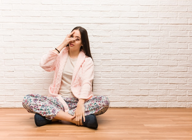 Joven vistiendo pijama avergonzada y riendo al mismo tiempo