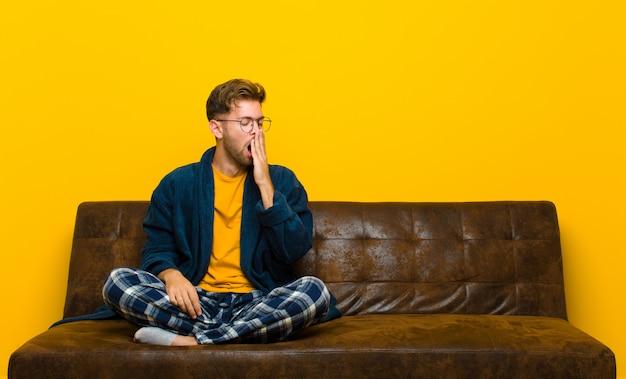 Joven vistiendo pijama bostezando perezosamente temprano en la mañana, despertando y luciendo somnoliento, cansado y aburrido. sentado en un sofa