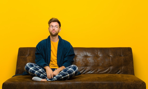 Joven vistiendo pijama preguntándose, pensando pensamientos e ideas felices, soñando despierto, mirando para copiar espacio en el costado. sentado en un sofa
