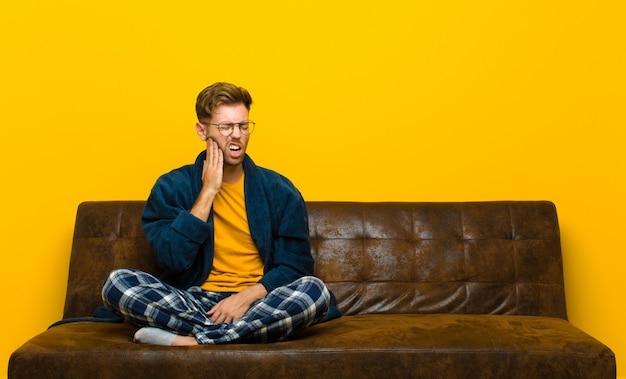 Joven vistiendo pijama sosteniendo la mejilla y sufriendo dolor de muelas doloroso, sintiéndose enfermo, miserable e infeliz, buscando un dentista. sentado en un sofa
