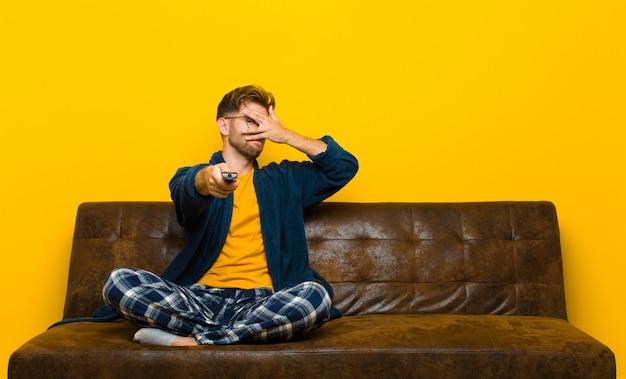 Joven vistiendo pijamas y sentado en un sofá con un control remoto