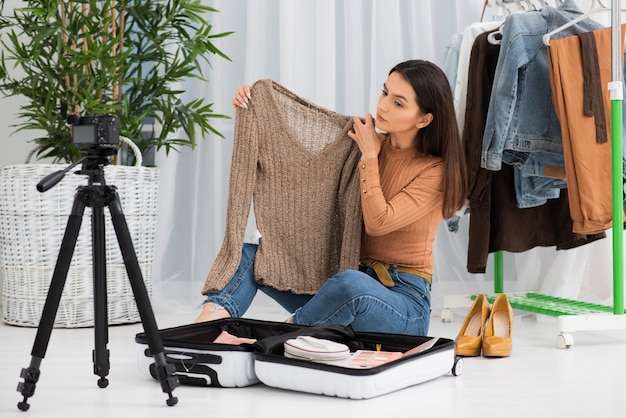 Joven vlogger grabando con ropa