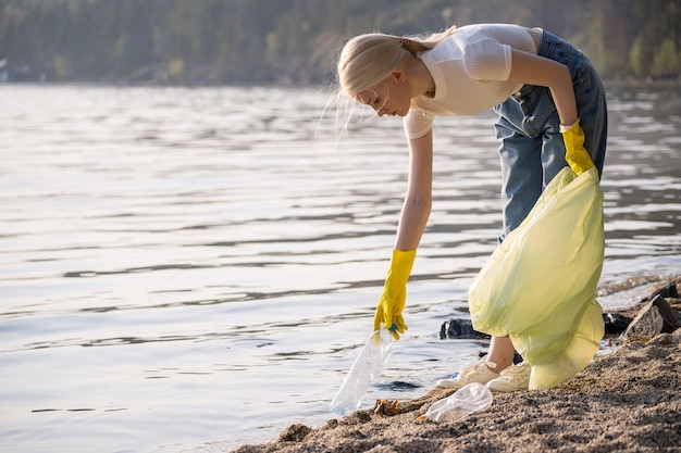 Joven voluntaria en guantes de goma con una bolsa de plástico limpia basura en la orilla del lago n ...