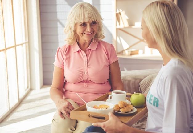 Joven voluntario está dando comida a hermosa anciana.