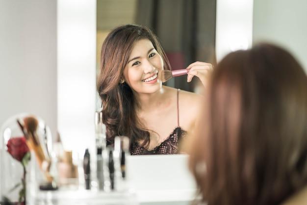 Joven y bella mujer asiática haciendo maquillaje cerca de espejo