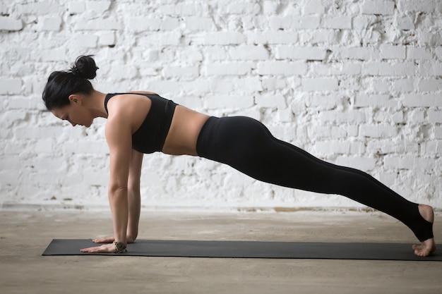 Joven, yogi, atractivo, mujer, tablón, pose, blanco, loft, fondo