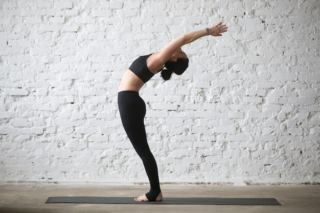 Joven, yogui, atractivo, mujer, ardha, chakrasana, posar, loft, backg