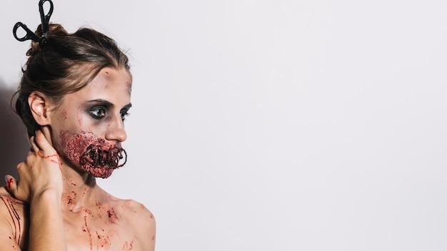 Joven zombie tocando el cuello