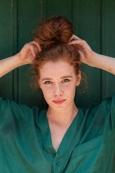 Jovencita arreglando su cabello rojo