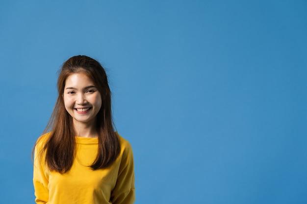 Jovencita de asia con expresión positiva, sonrisa amplia, vestida con ropa casual y mirando a cámara sobre fondo azul. feliz adorable mujer alegre se regocija con el éxito. concepto de expresión facial.
