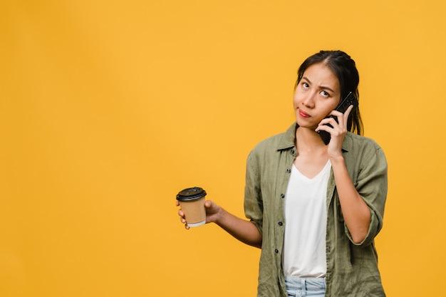 Jovencita asiática habla por teléfono y sostiene la taza de café con expresión negativa, gritos emocionados, llora enojado emocionalmente en ropa casual y se para aislado en la pared amarilla. concepto de expresión facial.
