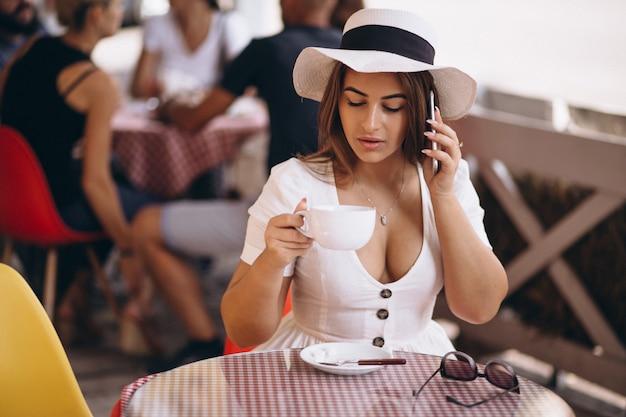 Jovencita en la barra tomando café y hablando por teléfono