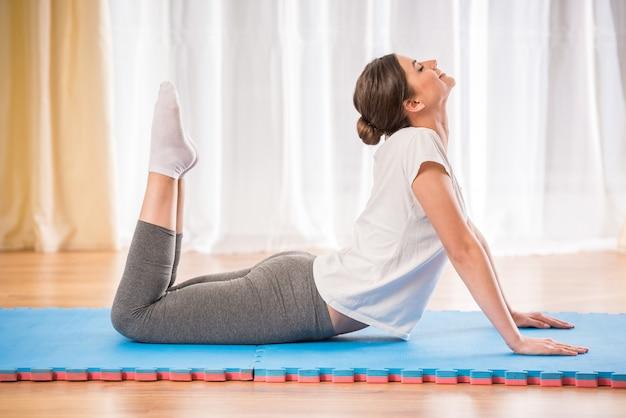 Jovencita bastante atlética haciendo yoga en una alfombra en casa.